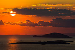 Sunset at sea, with small greek islands in background Stock Photo