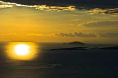 Sunset at sea, with small greek islands in background Stock Photography