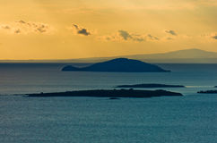 Sunset at sea, with small greek islands in background Royalty Free Stock Photo