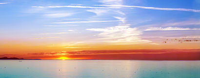 Sunset on the sea with some ships. Panoramic of sunset on the sea with some ships Royalty Free Stock Images