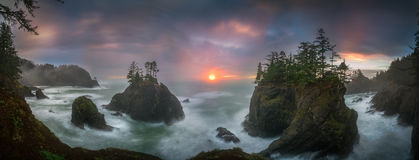 Sunset between Sea stacks with trees of Oregon coast. This is a photograph of big sea stacks with trees of Oregon coast taken at sunset hour Royalty Free Stock Images