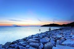 Sunset sea stones along coast Royalty Free Stock Photo