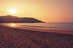 Sunset and sea. India Gokarna. The sun sets over the hill on the sea. Yellow warm sand in the foreground stock photos