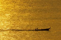 The sunset, the sea surface reflects the sunlight in gold. The ship ran through the sparkling sea surface.  stock photo