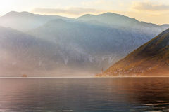 Sunset on the sea with theа foggy mountains Stock Photography