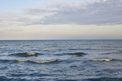 Very calm sea after the sunset. Sunset in the sea after a thunderstorm Stock Photo