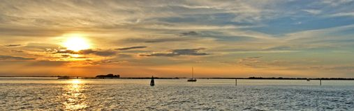 Sunset on the sea. A typical summer sunset on the Adriatic sea by the beach of the town of Grado in Italy with some small boats Stock Images