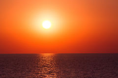 Sunset sea waves. Vibrant sunset on the sea with waves on the water surface, sun and orange red sky. All this makes a specific nature pattern Stock Photos