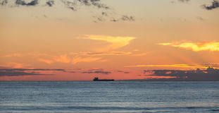 Sunset at sea on which a large cargo ship sailing in the sun against the evening sky, and on the shore fishermen catch fish and st Royalty Free Stock Photos