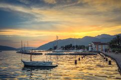 Sunset sea yacht mountains on a yellow background of the setting sun stock image