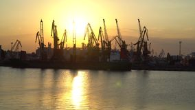 Sunset at the seaport. Wieden ship under unloading, the sun reflected in the Sea stock video