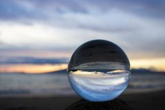 Sunset Seascape Captured in Glass Ball. Sunset seascape with clouds and horizon captured in glass ball on beach royalty free stock images