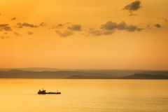 Sunset seascape. Sunset landscape with cargo ship and golden clouds Royalty Free Stock Image