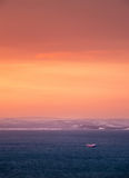 Sunset seascape. Sunset landscape with cargo ship and orange clouds Royalty Free Stock Photo