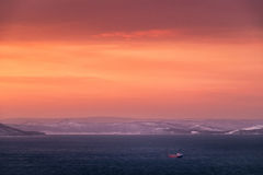 Sunset seascape. Sunset landscape with cargo ship and orange clouds Stock Image