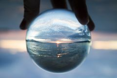 Seascape Sunset Captured in Small Glass Ball with Boat on Horizon. Sunset seascape with sun on horizon captured inside clear glass ball royalty free stock photography