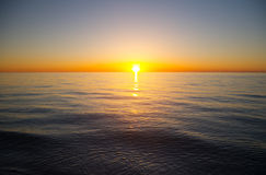 Sunset seascape. The sun to set over the horizon reflected in the sea Stock Photos