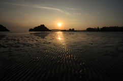 Sunset at the seaside in a low tide when bottom of the sea is visible Stock Photos