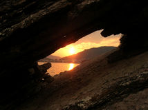 Sunset on seaside in stone frame. Sunset through the rock frame in Becici, Montenegro Stock Photography