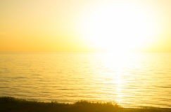 Sunset seaside. The sun to set over the horizon reflected in the sea Stock Photo