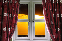 Sunset through a secure window. With curtains Stock Photography