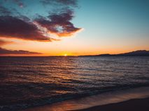 Sunset seen from the empty beach - mountains on the horizon royalty free stock image