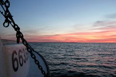 Montauk. A sunset is seen from the side of a fishing boat in Montauk, New York Stock Photo