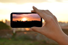 Sunset seen from a smart phone screen. Woman´s hand holding a smartphone, pointing to a colorful sunset Royalty Free Stock Images