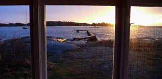 Sunset seen through a window. Sunset with beach scenery seen through a window stock photos