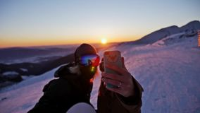 Sunset Selfie Winter People Slowmotion. Slowmotion footage of a skier and snowboarder taking a selfie with a beautiful sunset in the background stock footage