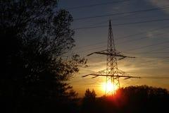 Sunset. Setting sun behind high-voltage line pylon stock image