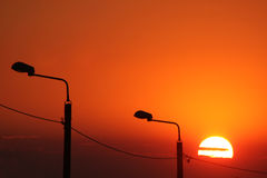 Sunset. Setting sun with the street lamplights Stock Images