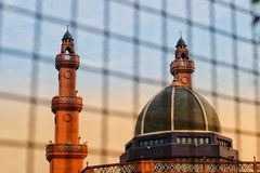 The sunset shines at the mosque and the islamic symbols on top; crescent moon and the star. stock photography