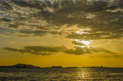 The sunset shining gold colour behind a marine Stock Photos