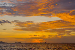 The sunset shining gold colour behind a marine Stock Image