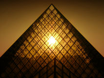 Sunset shining through Louvres pyramid stock images