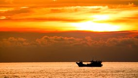 Sunset and Ship at Sea. The descending sun was making brilliance upon the water.There is a fishing boat on the sea stock photo