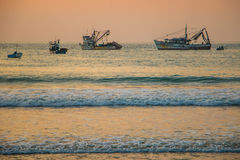 The sunset with ships at the coast of Colombia. The sunset with silhouette of boats at shore of Colombia stock images