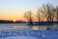 Sunset on the shore of the great river in winter Stock Photography