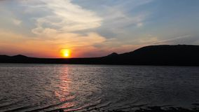 Sunset on the shore of a mountain lake stock video