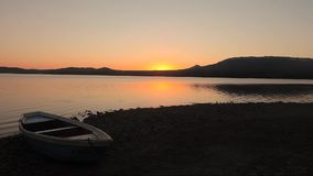 Sunset on the shore of a mountain lake stock footage
