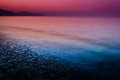Sunset Shoreline Covered With Pebblestones Stock Images