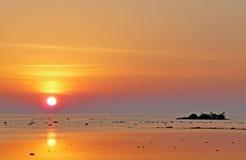 Sunset shoreline with island Stock Photos