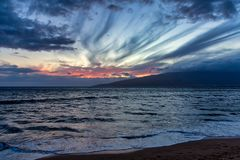Sunset from the shores of Maui. Sinking Sun setting behind the West Maui Mountains on a tropical island evening stock image