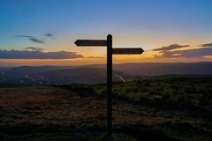 Way to go. Silhouetted signpost at dusk. Stock Images