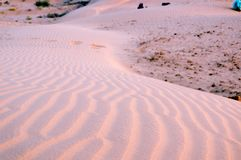 Sunset shot painted purple thorugh the sunset light. Sunset shot of small patterns on the sand. Sum with it`s beautiful beaches is a favorite tourist desert Royalty Free Stock Photography