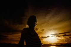 Sunset silhouette. Silhouette of a young girl against a brilliant sunset stock photo