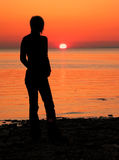 Sunset silhouette. Girl looking at a sunset Stock Images