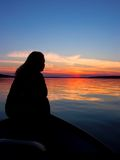 Sunset Silhouette. Silhouette of a young woman against a colorful sunset stock images