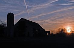 Sunset Silhouette. This was taken at dusk, silhouetting an old barn and silo Royalty Free Stock Images